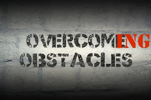 overcome obstacles stencil print on the grunge white brick wall